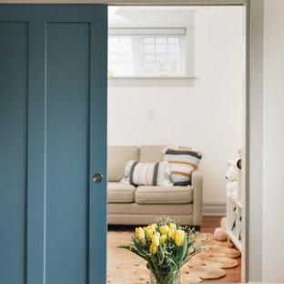 Cette image montre un petit sous-sol design avec un mur blanc, un sol en bois foncé et un sol marron.