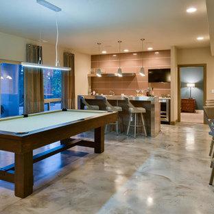 Idée de décoration pour un grand sous-sol design donnant sur l'extérieur avec un mur beige, béton au sol, aucune cheminée, un sol marron et salle de jeu.