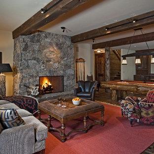 Ispirazione per una taverna stile rurale con cornice del camino in pietra, camino classico, parquet scuro, pareti beige e pavimento marrone