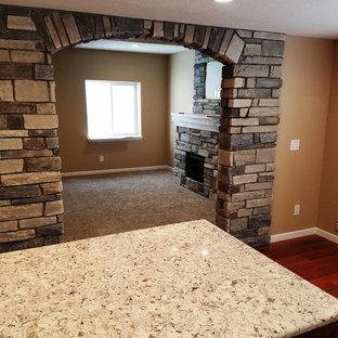 Idées déco pour un sous-sol classique semi-enterré avec un mur beige, sol en stratifié, un manteau de cheminée en pierre, un sol marron et une cheminée standard.