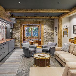 Aménagement d'un sous-sol montagne donnant sur l'extérieur et de taille moyenne avec un mur gris, un sol en bois foncé, aucune cheminée et un sol gris.