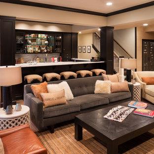 Cette photo montre un grand sous-sol chic enterré avec un mur beige, un sol en bois clair, un sol beige et un bar de salon.
