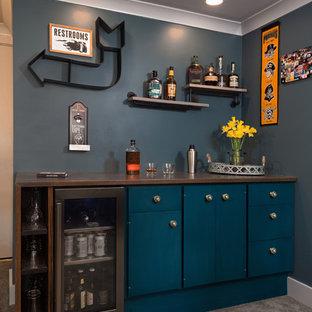 Réalisation d'un sous-sol bohème donnant sur l'extérieur et de taille moyenne avec un mur bleu, moquette, aucune cheminée et un sol gris.