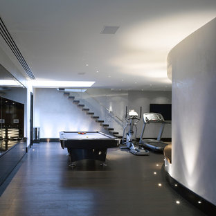 Design ideas for a contemporary basement in London with grey walls, dark hardwood flooring and brown floors.