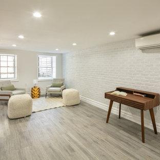 Cette photo montre un sous-sol tendance semi-enterré et de taille moyenne avec un mur blanc, un sol en vinyl, aucune cheminée, un sol gris et un mur en parement de brique.