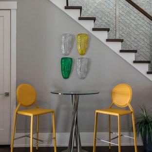 Cette image montre un grand sous-sol design avec un bar de salon et un sol en bois foncé.