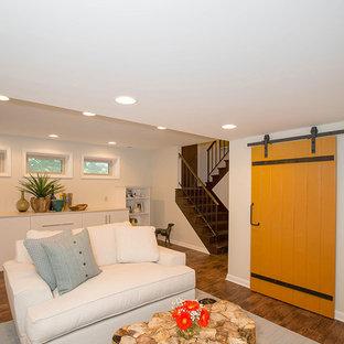 Inspiration pour un sous-sol design enterré et de taille moyenne avec un mur beige, un sol en bois brun, une cheminée d'angle, un manteau de cheminée en carrelage et un sol marron.