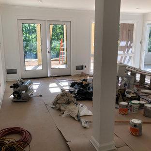 Réalisation d'un sous-sol minimaliste donnant sur l'extérieur et de taille moyenne avec un mur blanc, béton au sol, aucune cheminée et un sol gris.