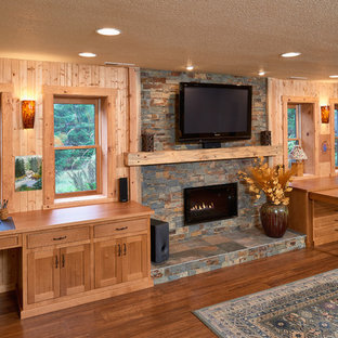 This is an example of a large rustic walk-out basement in Other with yellow walls, bamboo flooring, a ribbon fireplace and a stone fireplace surround.