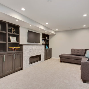Inspiration for a mid-sized transitional underground carpeted basement remodel in Calgary with gray walls, a standard fireplace and a stone fireplace