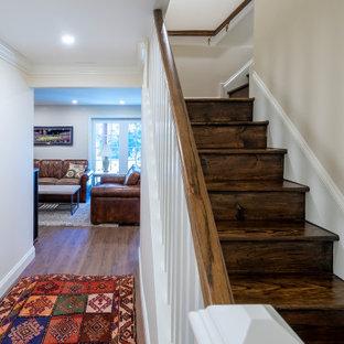Aménagement d'un sous-sol donnant sur l'extérieur et de taille moyenne avec un mur beige, sol en stratifié, une cheminée standard, un manteau de cheminée en brique et un sol marron.