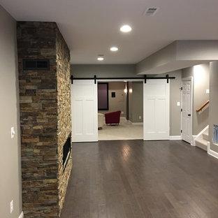 Réalisation d'un grand sous-sol design enterré avec un mur marron, un sol en bois foncé, une cheminée ribbon, un manteau de cheminée en pierre et un sol marron.