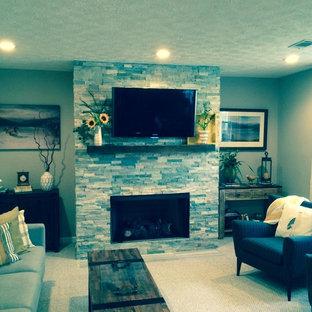 Idée de décoration pour un grand sous-sol tradition semi-enterré avec un mur gris, moquette, une cheminée standard et un manteau de cheminée en pierre.