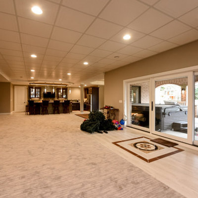 Inspiration for a huge contemporary walk-out carpeted and beige floor basement remodel in Chicago with beige walls