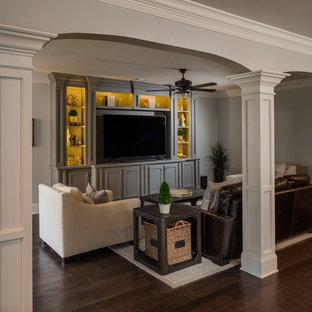 Aménagement d'un grand sous-sol classique donnant sur l'extérieur avec un mur gris, un sol en bois foncé, une cheminée standard, un manteau de cheminée en pierre et un sol marron.