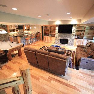 Idée de décoration pour un grand sous-sol chalet enterré avec un mur bleu, un sol en bois clair, un manteau de cheminée en pierre et une cheminée standard.