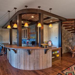 Idées déco pour un sous-sol montagne donnant sur l'extérieur avec un mur gris, aucune cheminée, un sol en bois foncé et un bar de salon.