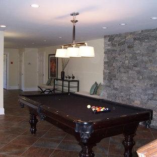 Immagine di un'ampia taverna classica con sbocco, pareti beige e pavimento in terracotta