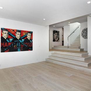 Idée de décoration pour un grand sous-sol minimaliste donnant sur l'extérieur avec un mur blanc et un sol en bois clair.