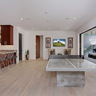 Inspiration for a contemporary walk-out light wood floor basement game room remodel in Orange County with white walls