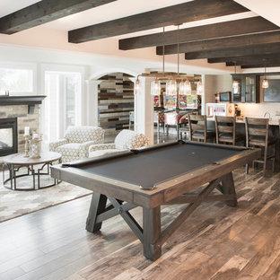 Idée de décoration pour un grand sous-sol tradition donnant sur l'extérieur avec un mur beige, un sol en bois brun, une cheminée double-face, un manteau de cheminée en pierre, un sol marron et salle de jeu.
