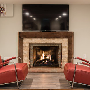 Inspiration for a large contemporary underground laminate floor and beige floor basement remodel in DC Metro with gray walls, a standard fireplace and a stone fireplace