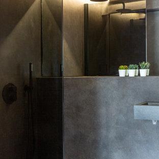Réalisation d'un sous-sol bohème semi-enterré et de taille moyenne avec un mur rose, béton au sol, aucune cheminée, un manteau de cheminée en plâtre et un sol gris.