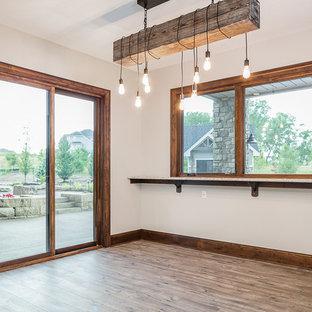 Réalisation d'un très grand sous-sol craftsman donnant sur l'extérieur avec un mur blanc, un sol en bois brun, aucune cheminée et un sol marron.