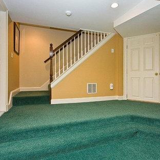 Aménagement d'un très grand sous-sol classique donnant sur l'extérieur avec un mur jaune, moquette et un sol turquoise.