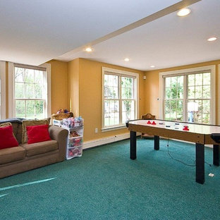 Inspiration for a huge timeless walk-out carpeted and turquoise floor basement remodel in Boston with yellow walls