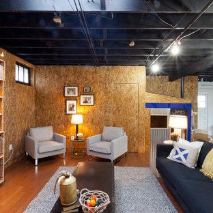 Ejemplo de sótano con puerta industrial, sin chimenea, con suelo de madera en tonos medios y suelo naranja