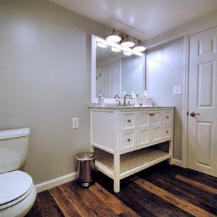 Cette photo montre un grand sous-sol chic enterré avec un mur gris, un sol en vinyl, aucune cheminée et un sol multicolore.