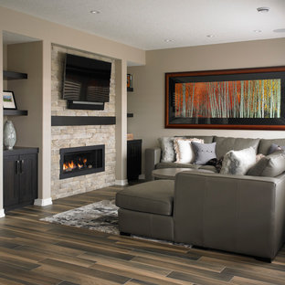 Cette photo montre un sous-sol chic avec un mur beige, un sol en carrelage de céramique, une cheminée standard et un manteau de cheminée en pierre.