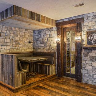Idée de décoration pour un sous-sol chalet avec un mur beige et un sol en bois foncé.