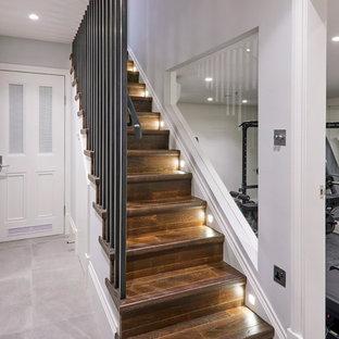 Inspiration pour un sous-sol design enterré et de taille moyenne avec un mur blanc, un sol en carrelage de céramique, aucune cheminée et un sol gris.