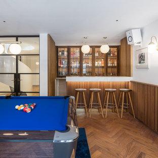 Idées déco pour un sous-sol classique en bois avec un mur blanc, un sol en bois brun, aucune cheminée, un sol marron et du lambris.