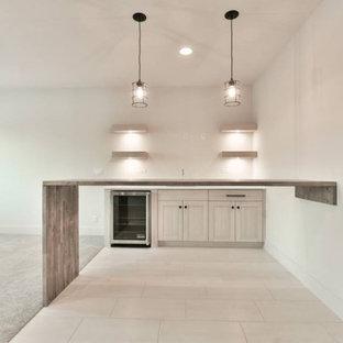 Cette image montre un sous-sol traditionnel donnant sur l'extérieur et de taille moyenne avec un mur blanc, moquette, aucune cheminée et un sol gris.