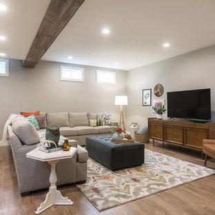 Idée de décoration pour un sous-sol bohème enterré et de taille moyenne avec un mur gris, un sol en vinyl, aucune cheminée et un sol marron.