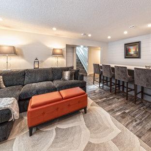 Inspiration pour un sous-sol minimaliste enterré et de taille moyenne avec un bar de salon, un mur blanc, un sol en vinyl, une cheminée standard, un manteau de cheminée en carrelage, un sol marron et du lambris de bois.