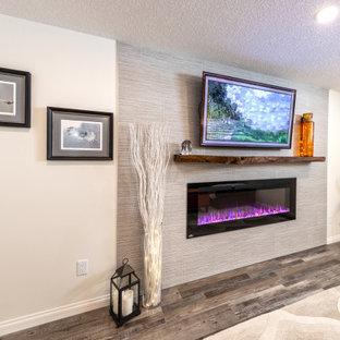 Cette photo montre un sous-sol moderne enterré et de taille moyenne avec un bar de salon, un mur blanc, un sol en vinyl, une cheminée standard, un manteau de cheminée en carrelage, un sol marron et du lambris de bois.