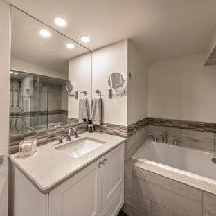 Réalisation d'un sous-sol minimaliste enterré et de taille moyenne avec un bar de salon, un mur blanc, un sol en vinyl, une cheminée standard, un manteau de cheminée en carrelage, un sol marron et du lambris de bois.