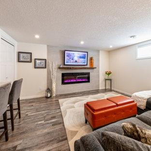 Aménagement d'un sous-sol moderne enterré et de taille moyenne avec un bar de salon, un mur blanc, un sol en vinyl, une cheminée standard, un manteau de cheminée en carrelage, un sol marron et du lambris de bois.