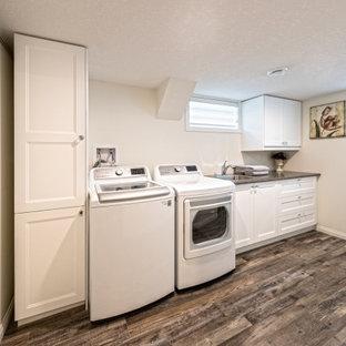 Idée de décoration pour un sous-sol minimaliste enterré et de taille moyenne avec un bar de salon, un mur blanc, un sol en vinyl, une cheminée standard, un manteau de cheminée en carrelage, un sol marron et du lambris de bois.