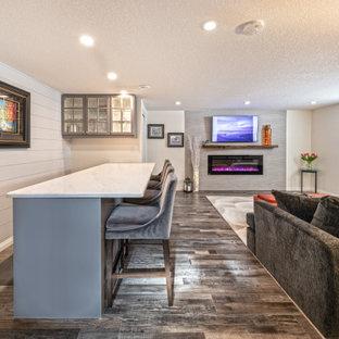 Cette image montre un sous-sol minimaliste enterré et de taille moyenne avec un bar de salon, un mur blanc, un sol en vinyl, une cheminée standard, un manteau de cheminée en carrelage, un sol marron et du lambris de bois.