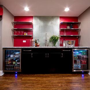 Idée de décoration pour un grand sous-sol bohème avec un mur gris, un sol en bois brun, aucune cheminée et un sol marron.