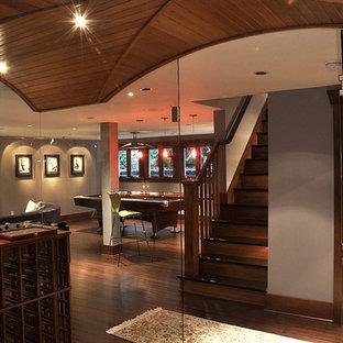 Immagine di una taverna contemporanea seminterrata con pareti grigie e pavimento in bambù