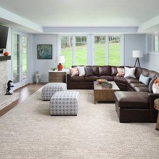 Idée de décoration pour un sous-sol tradition de taille moyenne et donnant sur l'extérieur avec un mur bleu, un sol en bois brun, une cheminée standard, un manteau de cheminée en pierre et un sol marron.