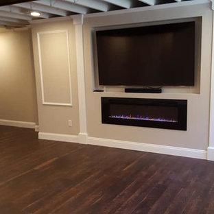 Idée de décoration pour un sous-sol tradition semi-enterré et de taille moyenne avec un mur beige, un sol en bois foncé, une cheminée ribbon, un manteau de cheminée en plâtre et un sol marron.