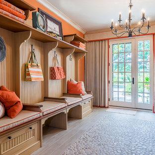 Réalisation d'un sous-sol tradition donnant sur l'extérieur et de taille moyenne avec un mur orange et un sol en bois clair.