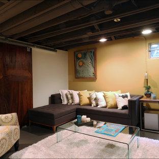 Aménagement d'un petit sous-sol contemporain semi-enterré avec un mur jaune, béton au sol, aucune cheminée et un sol gris.